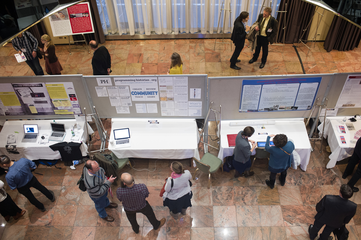 Photograph of poster presenters and visitors milling in the hall, shot from the balcony above.