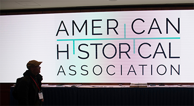 American Historical Association logo on a screen with a person in front of it