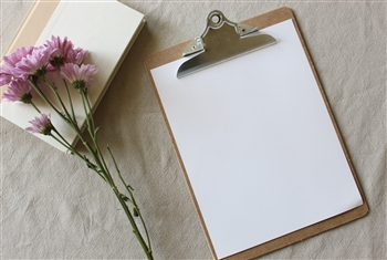 Flower and a clipboard with an empty piece of paper. Photo by Bethany Cirlincione via Unsplash