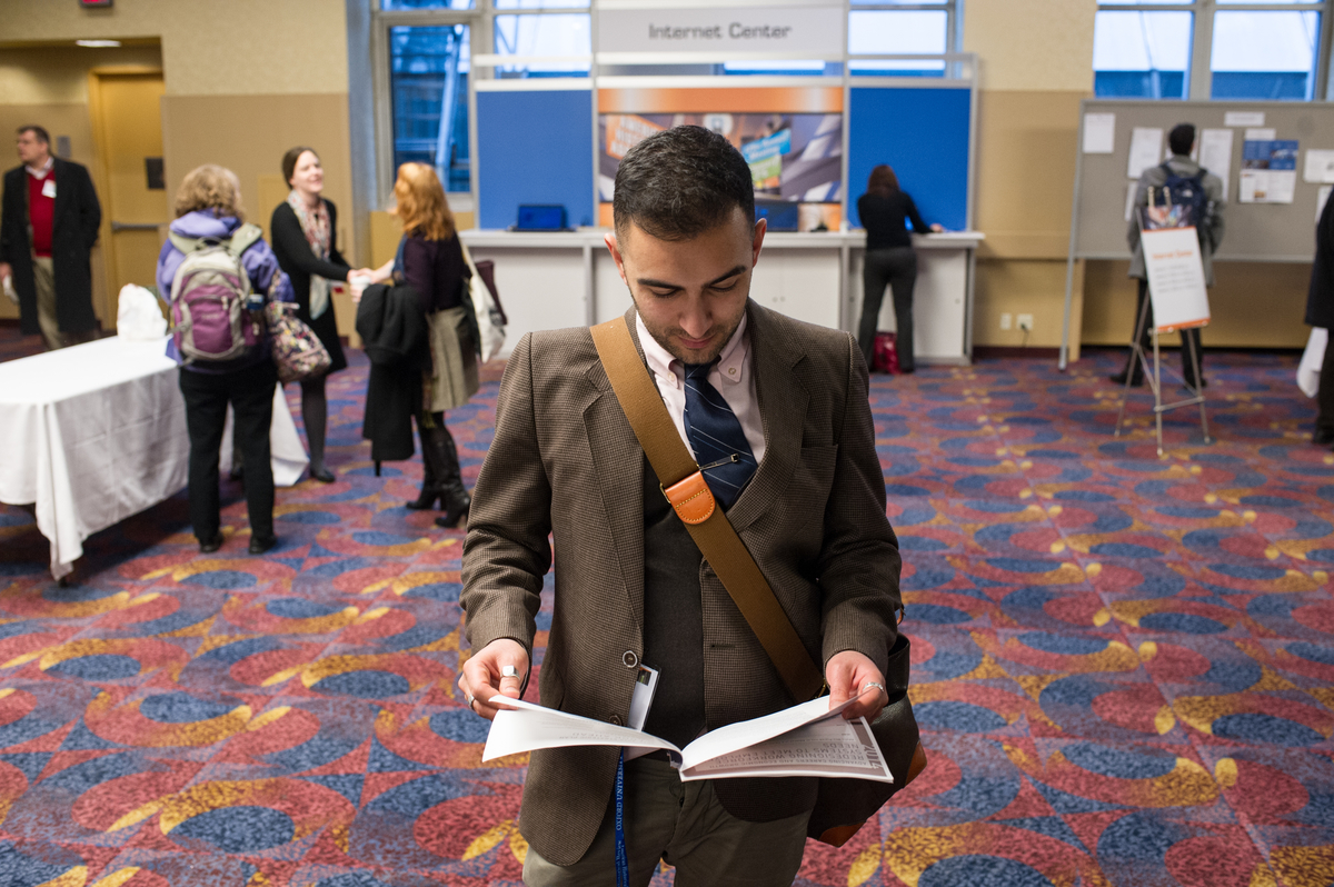 A historian examines an information packet while walking through the Career Fair at the 2015 annual meeting in New York.