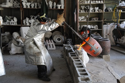 Wearing a fireproof suit, a foundry worker pours molten bronze into a Rosa Parks mold. Credit: Scott Polanca.