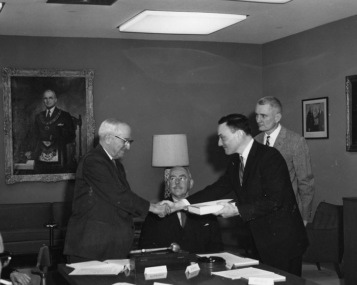Richard Hewlett shakes former president Harry S. Truman's hand, as he and co-author Oscar Anderson (standing) present him with the first volume of the Atomic Energy Commission history in 1962. Dean Acheson sits between them. Harry S. Truman Library