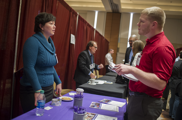 Stephanie Young from RAND Corporation conducts an informational interview with a Career Fair attendee. Marc Monaghan