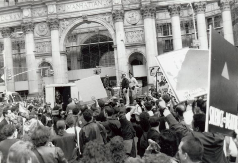 "An ACT UP protest rally in front of the Manhattan Municipal Building in 1989. The group's logo—a pink triangle with the words ""Silence = Death""—is visible on the sign at right. Manuscripts and Archives Division, The New York Public Library"