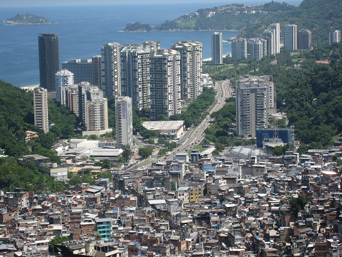 In Rio de Janeiro, high-rise buildings loom in front of Rocinha, one of the largest favelas in Brazil. Wikimedia Commons