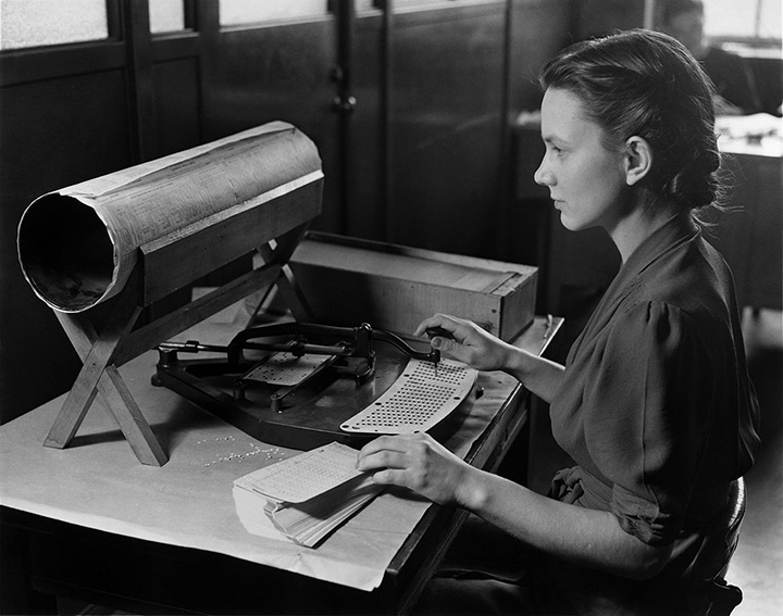 A woman uses a Hollerith card punch machine for the 1940 census. NARA/Wikimedia Commons