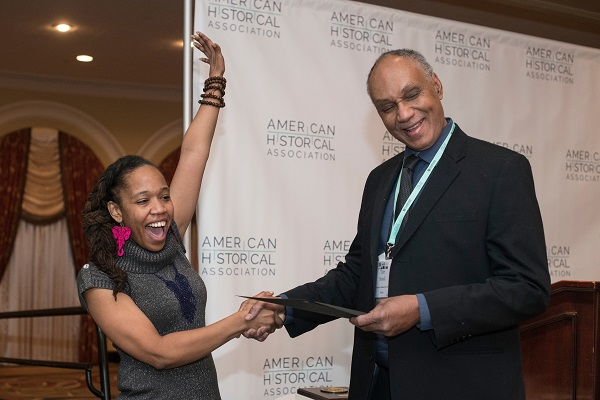 With the help of AHA president Tyler Stovall, Sowande' M. Mustakeem (Washington Univ. in St. Louis) celebrates winning the Wesley-Logan Prize in African Diaspora History.