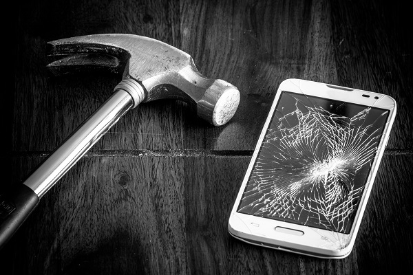 A hammer rests next to a cracked phone screen.
