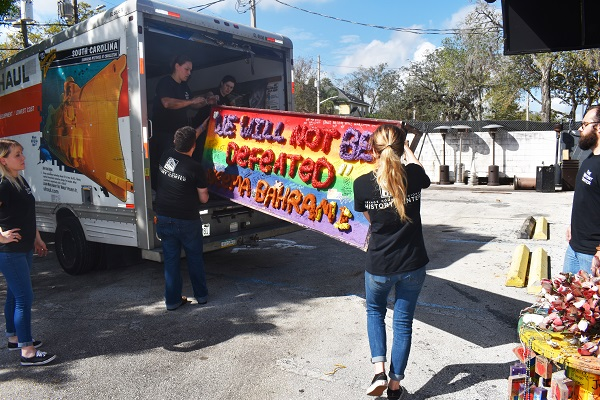 Orange County Regional History Center staff load up a large banner, bearing the name of survivor Neema Bahrami, from the Pulse nightclub site for permanent preservation.