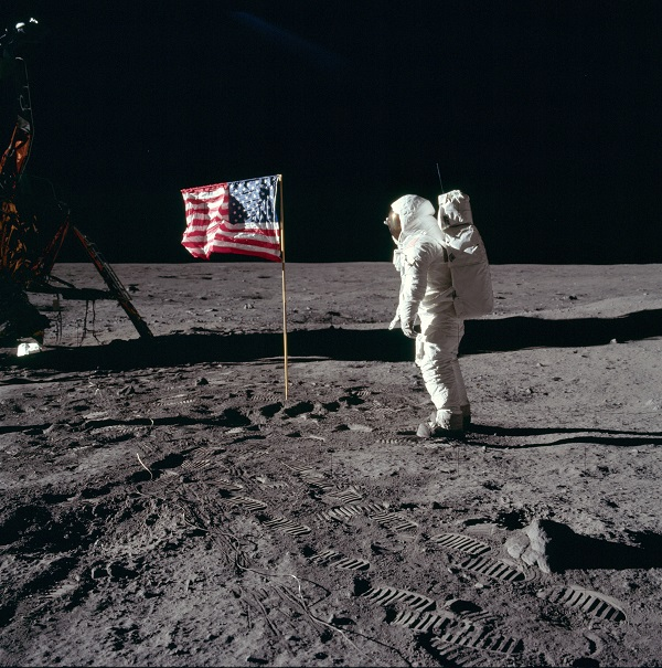 Buzz Aldrin stands with the American flag on the surface of the moon.