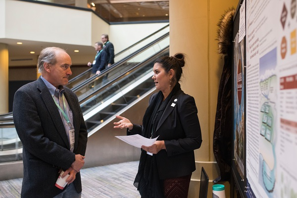 John McNeill discusses indigenous Hawaiian medicine with Kealoha Fox at the AHA18 poster session.