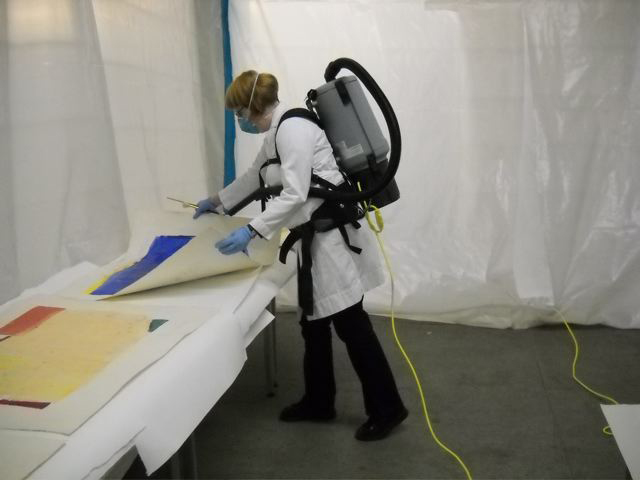 In 2012 after Hurricane Sandy, a specialist working in New York's Cultural Recovery Center vacuumed dried mold from works on paper.