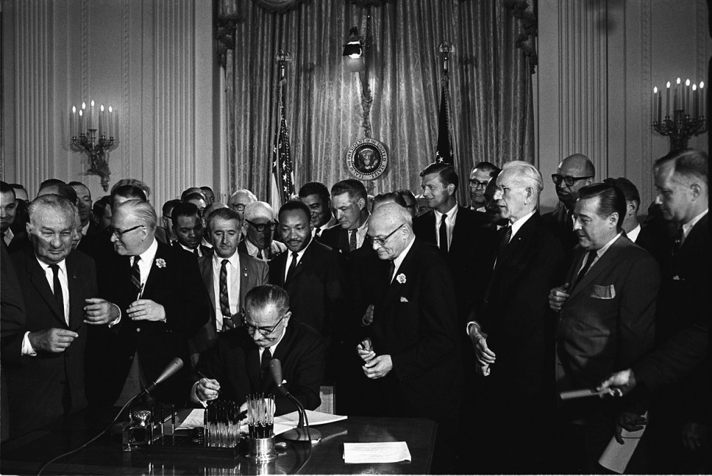 President Johnson signs the 1964 Civil Rights Act; notice King standing behind him.