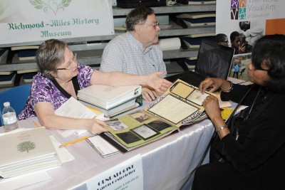 A genealogist provides free consultations at a community history event hosted by History United and regional libraries.