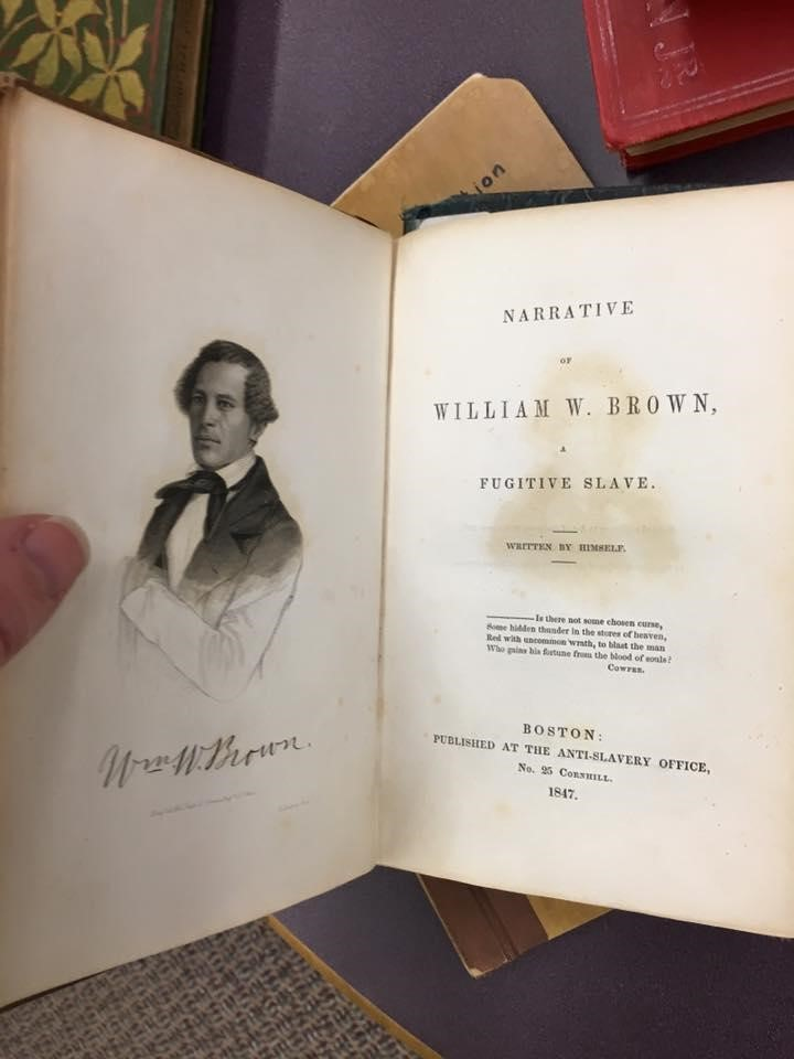 An individual holds the first edition of William Wells Brown's Narrative of William Wells Brown, A Fugitive Slave (1847)