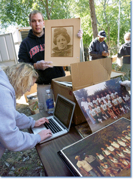 During the North Omaha History Harvest, University of Nebraska-Lincoln students inventoried and processed hundreds of artifacts from a storage container on the grounds of the Great Plains Black History Museum, which had been closed for more than a decade. Here, Matt Koziol and Jessica Hare work with a collection of photographs.