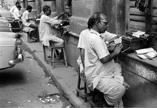 Photographer: Salim Paul; Source: Chitrabani Typewriting salesmen using building ledge, Calcutta, 1979.