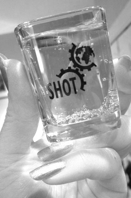 SHOT conference swag: the famous SHOT glass, with the old SHOT logo.  Photo by Marie Hicks (@histoftech)
