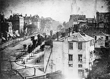 "Credit: Public domain, downloaded from Wikimedia Commons.  Boulevard du Temple, Paris, 3rd arrondissement, by Louis Daguerre,"" is a high-resolution digital image of a 1838 daguerreotype, reproduced here as a halftone. It is thought to be the earliest photograph with a human subject."