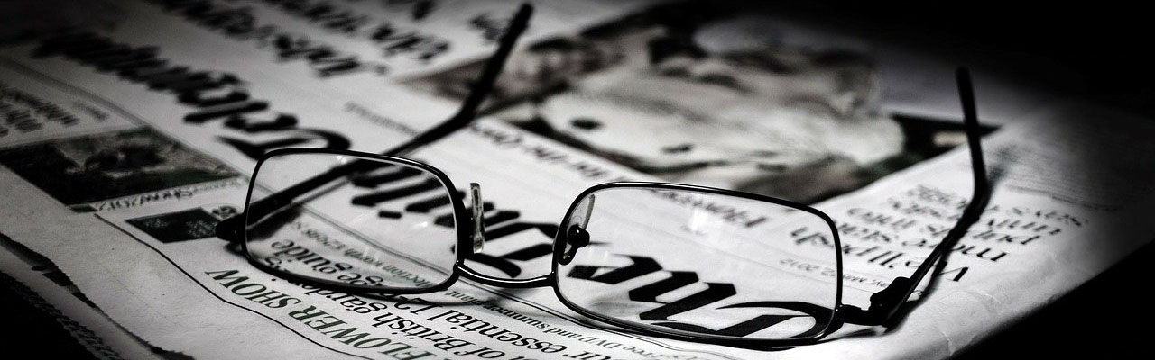 Image of glasses on top of a newspaper