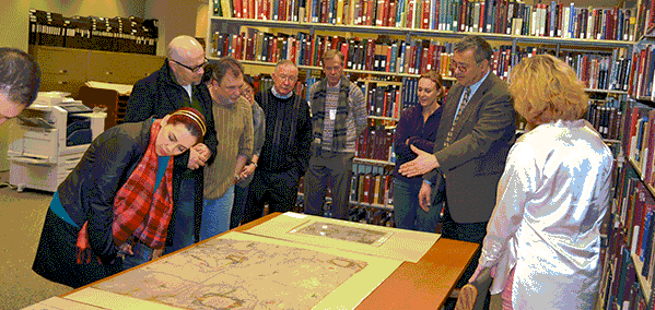 A group of people in a library around table with a map on it